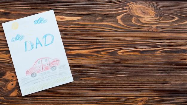 Inscripción de papá con dibujo de coche en mesa