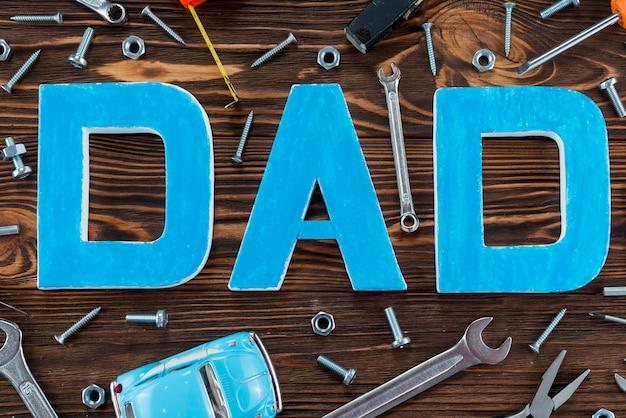 Inscripción de papá con diferentes herramientas y carro de juguete.