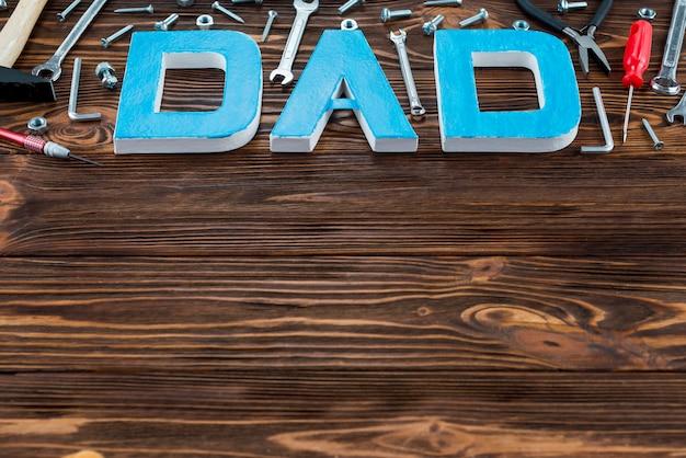Inscripción de papá con diferentes herramientas en mesa de madera.