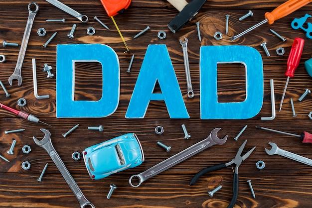 Inscripción de papá con herramientas y carro de juguete.