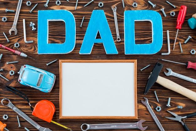 Inscripción de papá con herramientas y marco en blanco.