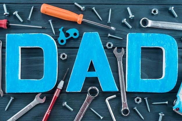 Inscripción de papá con herramientas en mesa azul