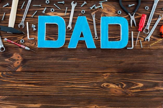 Inscripción de papá con herramientas en mesa de madera