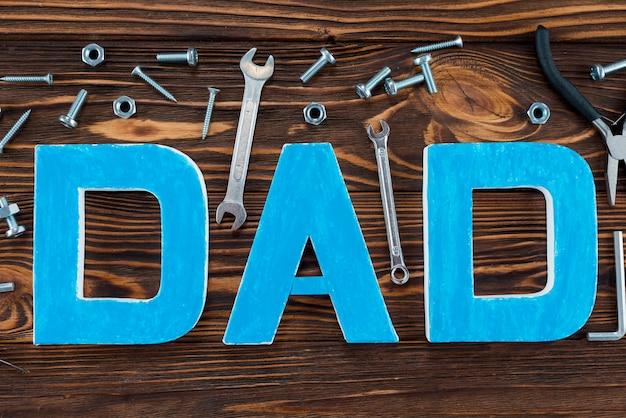 Inscripción de papá con herramientas en mesa marrón