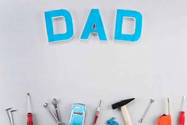 Inscripción de papá con herramientas en mesa