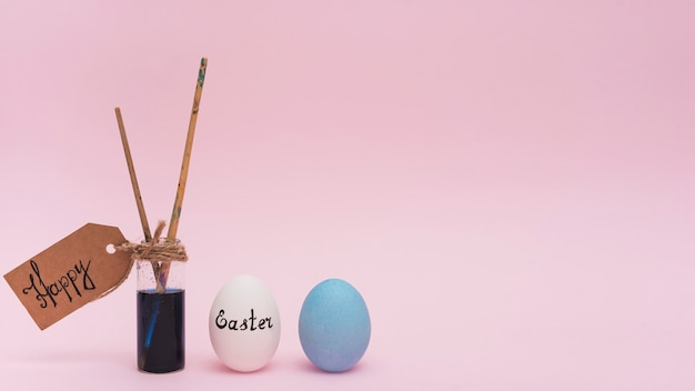 Inscripción de pascua feliz con huevos y pincel