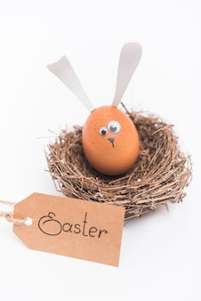 Inscripción de pascua con huevo con orejas de conejo en nido