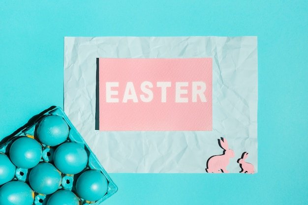 Inscripción de pascua con huevos brillantes en rack y conejos de madera