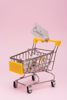 Inscripción de pascua con huevos en carro de supermercado