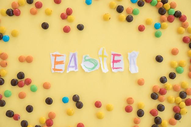 Inscripción de pascua en papeles cerca de caramelos pequeños.