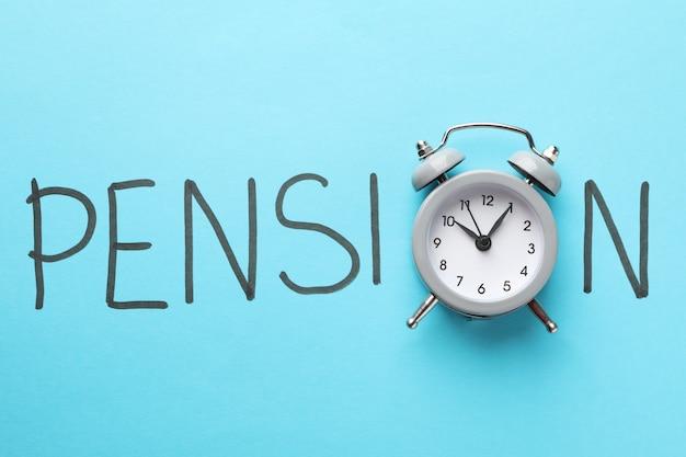 Inscripción pensión con despertador sobre superficie azul