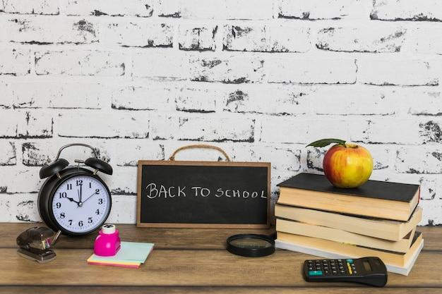 Inscripción de regreso a la escuela en la pizarra cerca de útiles escolares