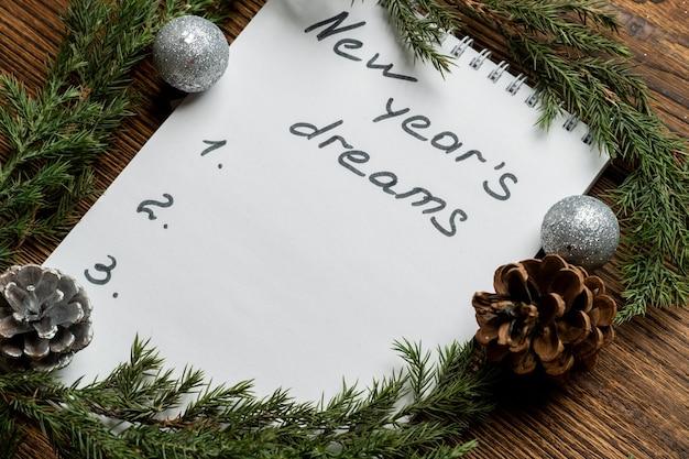 Inscripción de sueños de año nuevo en cuaderno con ramas de abeto y juguetes de árbol de navidad