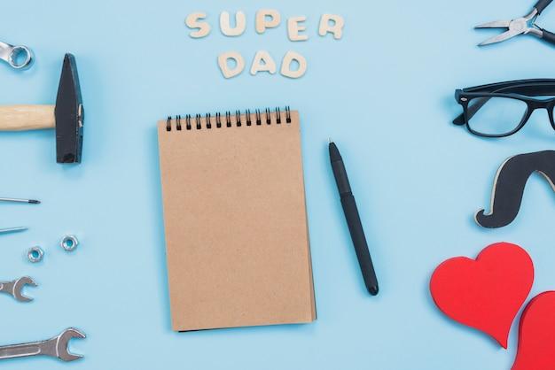 Inscripción de super papá con libreta y herramientas.