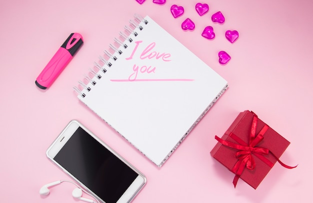 La inscripción te amo en un cuaderno junto a un regalo y un teléfono inteligente el día de san valentín