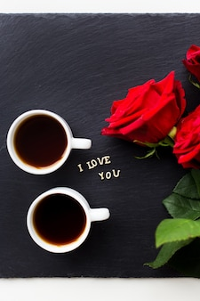 La inscripción te amo sobre una superficie negra con rosas rojas y tazas de café