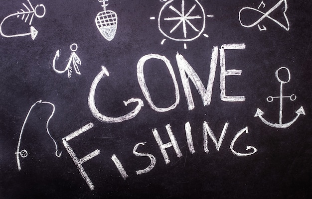 Inscripción de tiza de pesca en pizarra con dibujos marinos