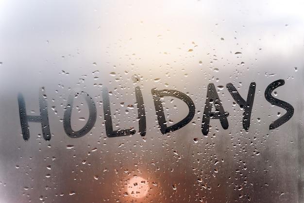 La inscripción de vacaciones en el cristal sudoroso.