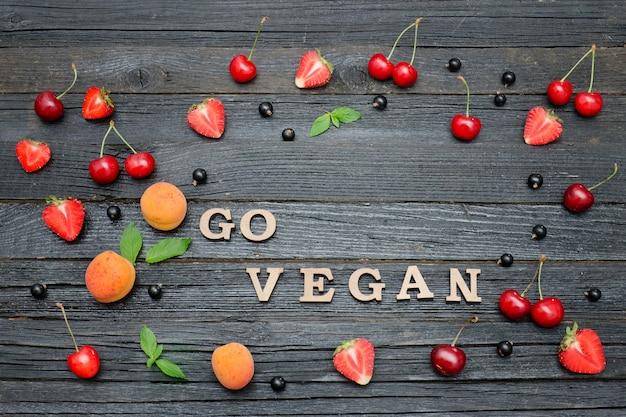 Inscripción ve vegano y frutas. mesa de madera negra. concepto de comida