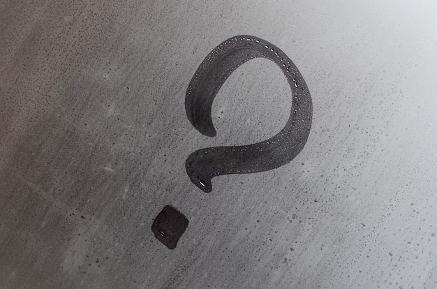 La inscripción en vidrio, concepto de signo de interrogación. el signo de interrogación está pintado en la superficie de la ventana empañada y húmeda.