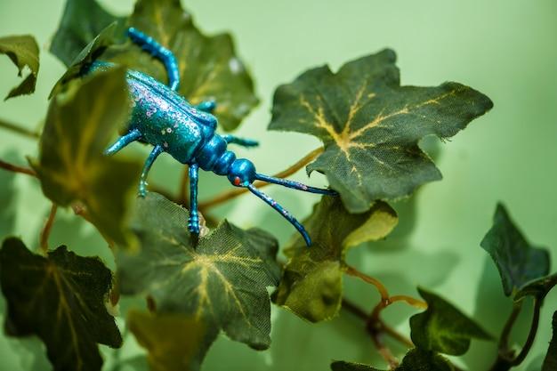 Insecto plástico entre hojas verdes