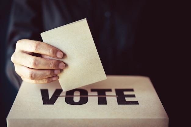 Inserto de papel marrón en la casilla de votación, concepto de democracia, tono retro