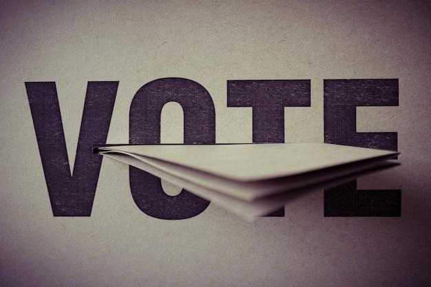 Inserto de papel marrón en la casilla de votación, enfoque selectivo, tono retro, concepto de democracia