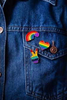 Insignias de la bandera lgbtq del arco iris contra el mes del orgullo de fondo de mezclilla