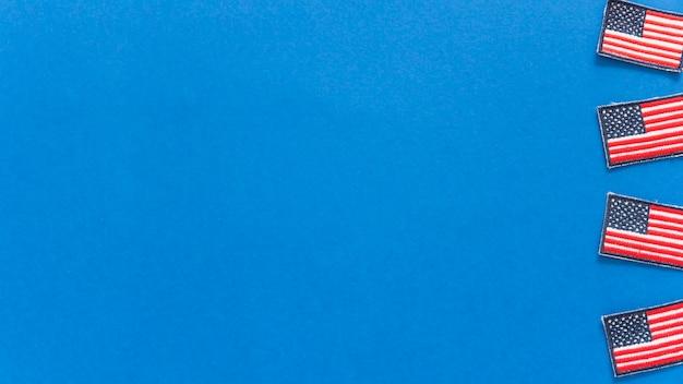 Insignias con banderas americanas sobre fondo azul