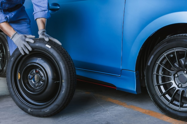 Inspección del automóvil del hombre asiático medir la cantidad de neumáticos de goma inflados del automóvil.