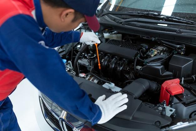 Inspección detallada del vehículo del mecánico de coche asiático.