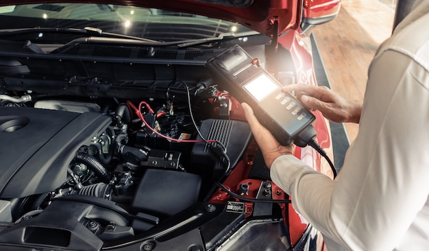 Inspección del hombre con el voltímetro del probador de capacidad de la batería. para el mantenimiento del servicio de reparación industrial a motor.
