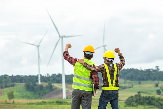 La inspección y el progreso de dos ingenieros de molinos de viento verifican la turbina eólica en el sitio de construcción y tuvieron éxito en la misión.