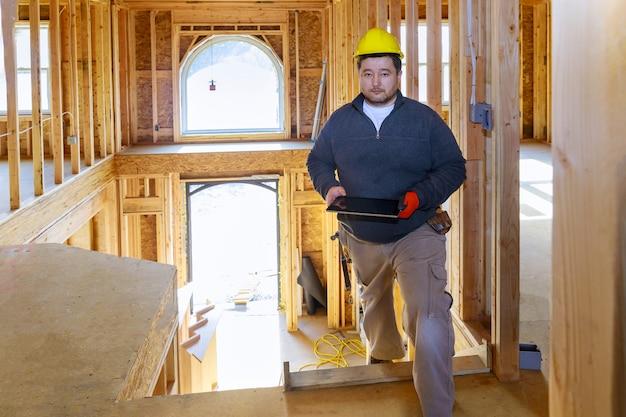 Inspector de edificios mirando nueva casa, sosteniendo tableta con casco