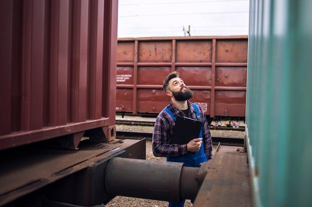 Inspector de ferrocarril control de tren de mercancías en la estación