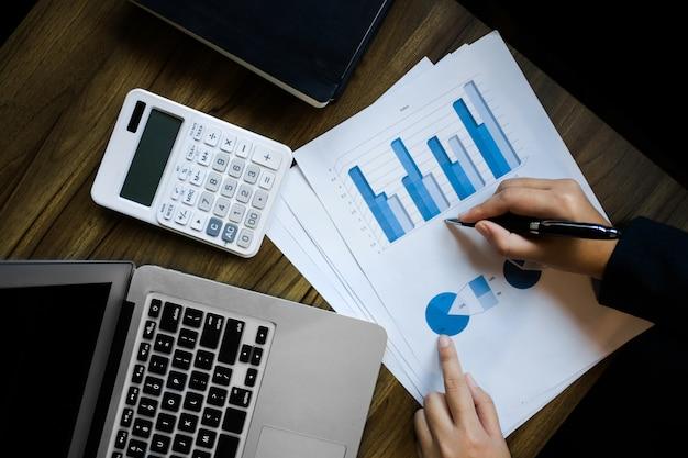 Inspector financiero que calcula en datos de inversión con documentos y computadora portátil en la habitación oscura de la oficina