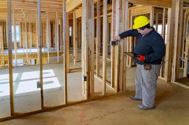 El inspector inspecciona los sistemas eléctricos de la casa electricista con tablet pc
