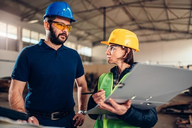 Inspector de seguridad en el lugar de trabajo escribiendo un informe en una fábrica industrial