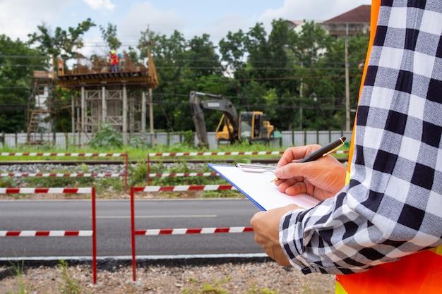 Los inspectores o ingenieros están examinando la construcción de vías públicas en las comunidades.