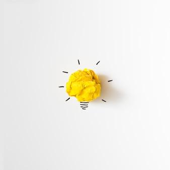 Inspiración arrugado idea de bombilla de papel amarillo sobre fondo blanco
