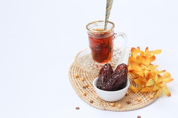 Inspiración del ramadán que muestra palmeras datileras en un cuenco de ovario con flores de orquídeas y una taza de té