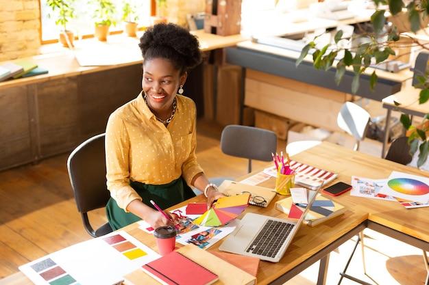 Inspirado y creativo. gerente creativo afroamericano sentado cerca de la computadora portátil y sonriendo teniendo inspiración