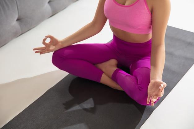 Inspirado. hermosa joven trabajando en el interior, haciendo ejercicios de yoga en la alfombra gris en casa. cabello largo en forma de modelo caucásico practicando. concepto de estilo de vida saludable, mental, atención plena, equilibrio.