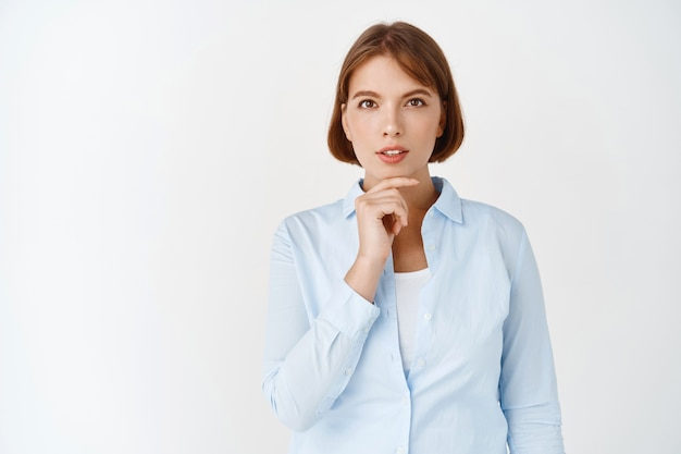 Inspírate. retrato de joven directora directora que mira pensativa, tiene una idea, toca la barbilla y reflexiona sobre el plan, de pie en la pared blanca