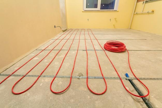 Instalación de cable eléctrico rojo de calefacción en el piso de cemento en una pequeña habitación nueva sin terminar con paredes enlucidas. renovación y construcción, confortable concepto de hogar cálido.