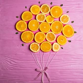 Instalación de globos hechos de rodajas de naranja y atados con un lazo rosa sobre un fondo de textura de madera rosa.