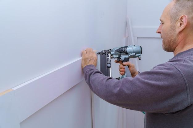 Instalación de molduras en la pared del fragmento de moldura, vista superior del carpintero con pistola de clavos