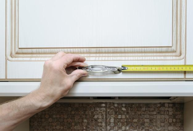 Instalación de muebles de cocina midiendo la distancia donde fijar la manija de la puerta del mueble