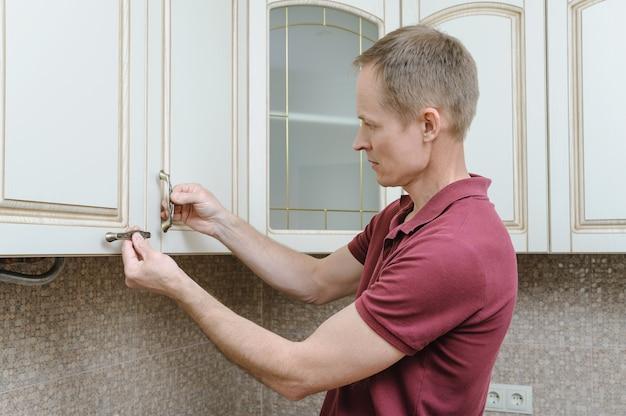 Instalación de muebles de cocina poniendo tiradores en los armarios de las puertas