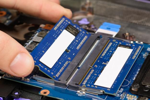 Instalación de nuevos chips de memoria ram en la computadora portátil. reparación y actualización de laptop en casa